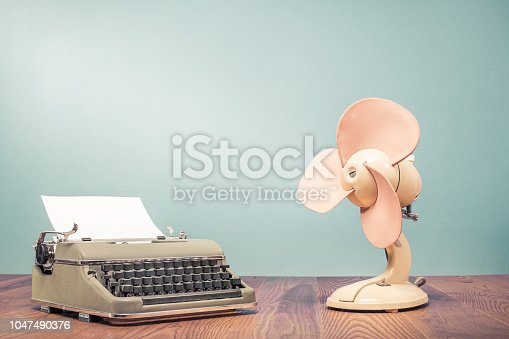 istock Retro classic typewriter with sheet of paper and old cooling fan on wooden table front mint green wall background. Vintage style filtered photo 1047490376