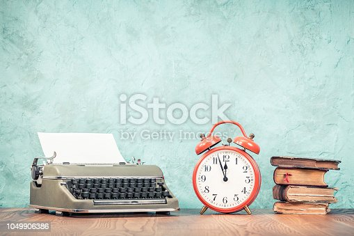 istock Retro classic typewriter with sheet of paper, old books and big orange alarm clock on wooden table front aquamarine concrete wall background. Vintage style filtered photo 1049906386