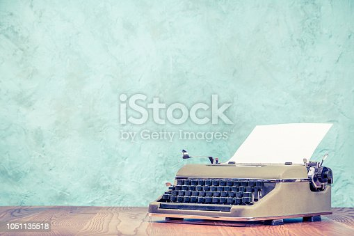 istock Retro classic typewriter with sheet of paper on wooden table front aquamarine concrete wall background. Vintage old style filtered photo 1051135518