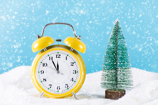 Retro clock and Christmas fir tree on snow and it's snowing winter day