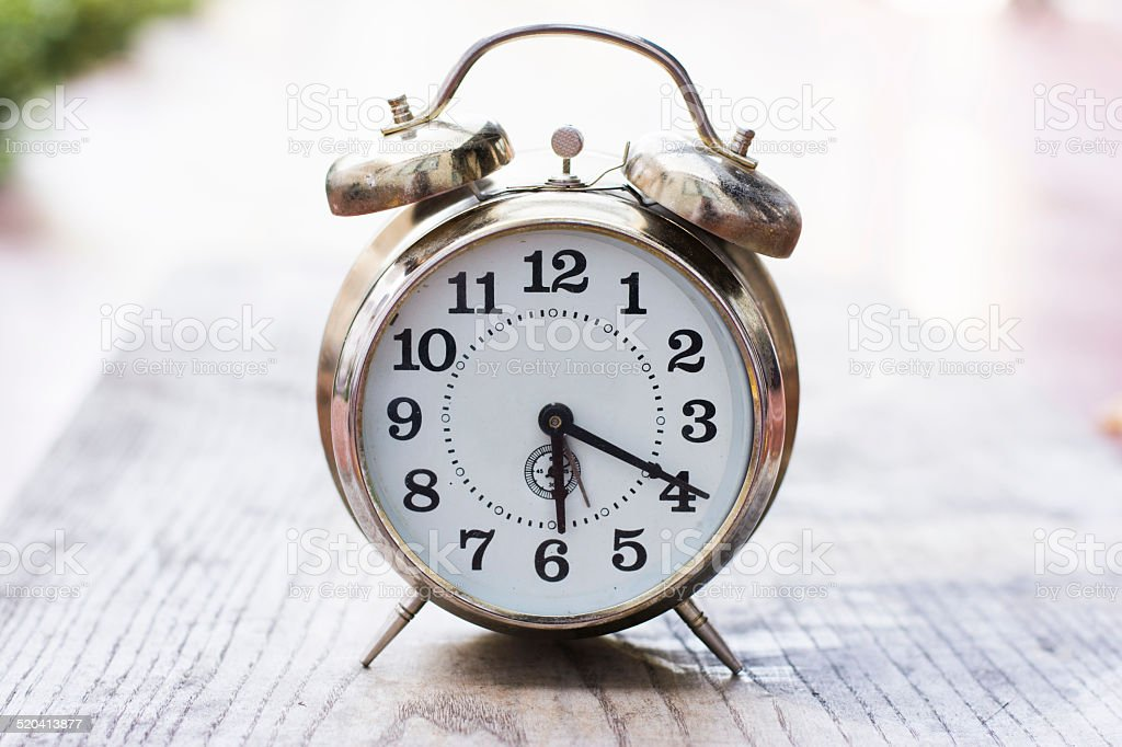 Retro clock on a wooden table stock photo