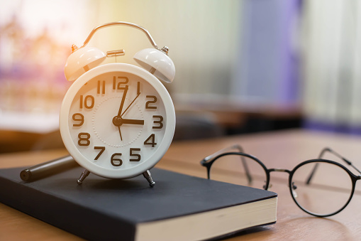 retro clock time at 9 o'clock with notebook or memo on wood table, times of memory writing diary concept vintage color tone.