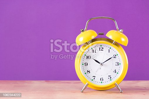 1048940572 istock photo Retro clock with bell on wooden desk and purple background 1062344222