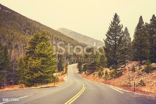 Retro color toned empty road in Rocky Mountains National Park on a cloudy day, Colorado, USA.