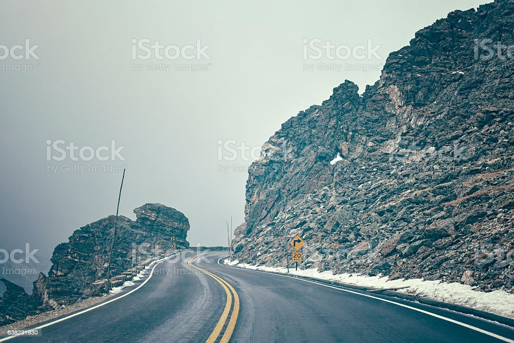 Retro color toned mountain road in fog. stock photo