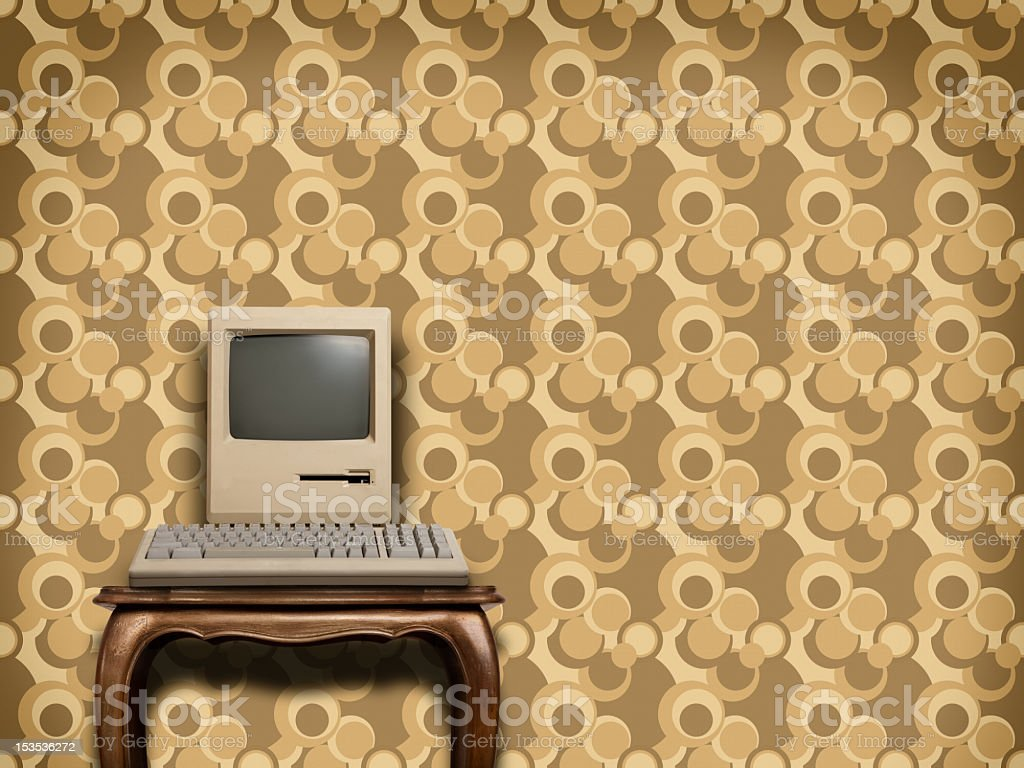 Retro computer on wooden table with sixties wallpaper stock photo