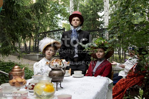 Ekaterinburg, Russia - July, 20, 2019. Retro costumes and historical reconstruction in city park. Men and Women dressed clothes 19 century. Participants of the historical reconstruction which imitates the tea ceremony in merchant houses of Russia. People gathered in the garden, drink tea, play games. Picnic in a city park..