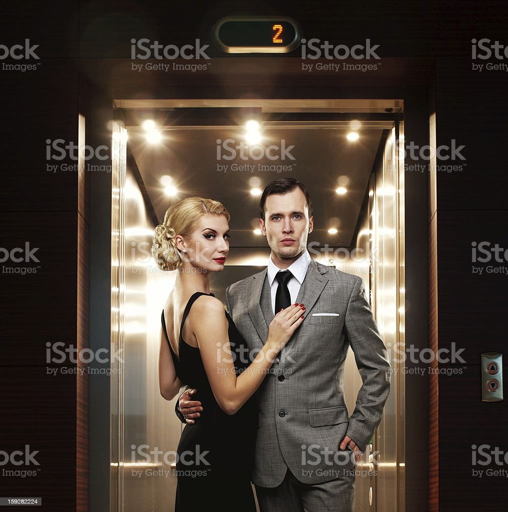 Retro couple standing against elevator stock photo