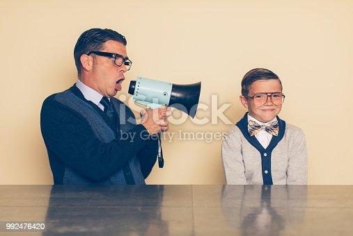 istock Retro Dad Encouraging His Son through a Megaphone 992476420