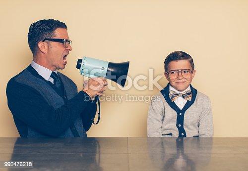 992091590 istock photo Retro Dad Parenting Son through a Megaphone 992476218