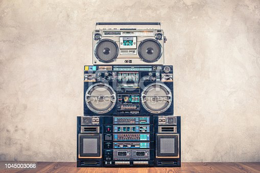 istock Retro design ghetto blaster stereo radio cassette tape recorders boombox tower from circa 80s front concrete wall background. Vintage instagram old style filtered photo 1045003066