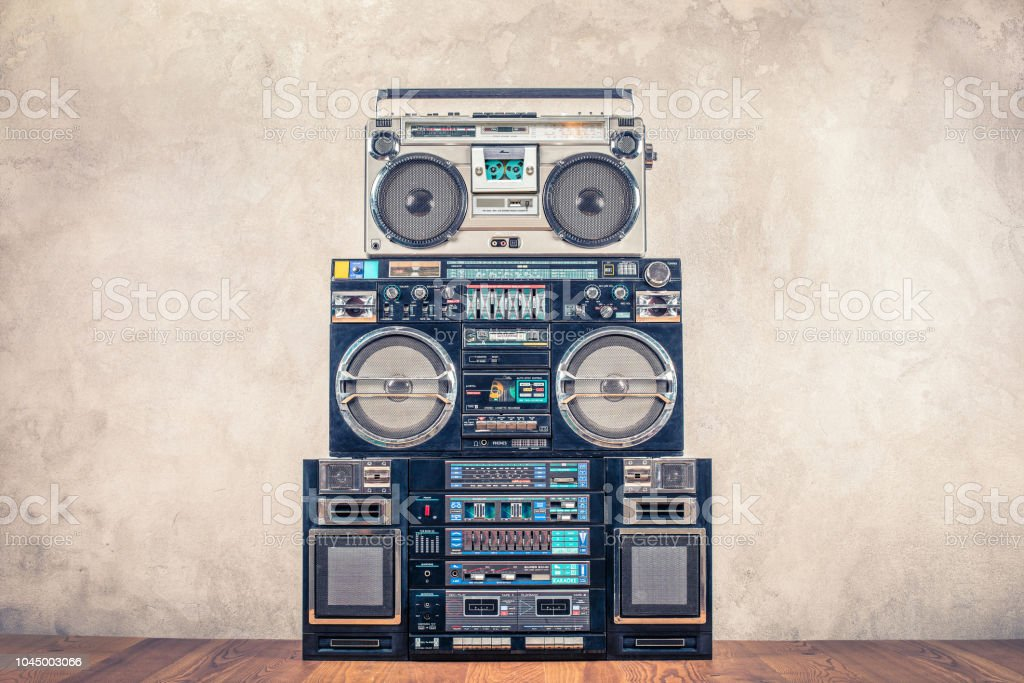 Retro design ghetto blaster stereo radio cassette tape recorders boombox tower from circa 80s front concrete wall background. Vintage instagram old style filtered photo stock photo