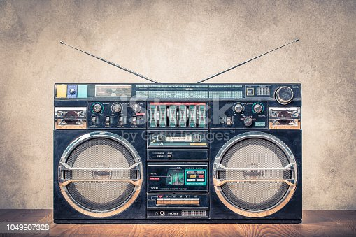 1043737676 istock photo Retro design ghetto blaster stereo radio cassette tape recorders boombox from circa 80s front concrete wall background. Vintage instagram old style filtered photo 1049907328