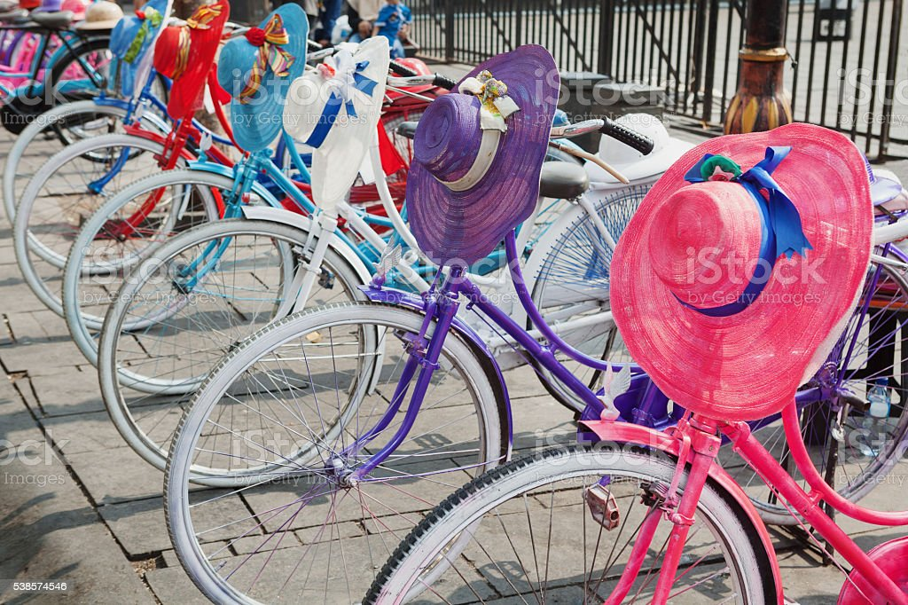 Retro design old colourful bikes with woman hats and helmets stock photo