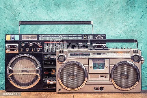 1043737676 istock photo Retro designed ghetto blaster stereo boombox radio receivers with cassette recorders from circa 80s front textured aquamarine wall background. Listening music concept. Vintage old style filtered photo 1055447912
