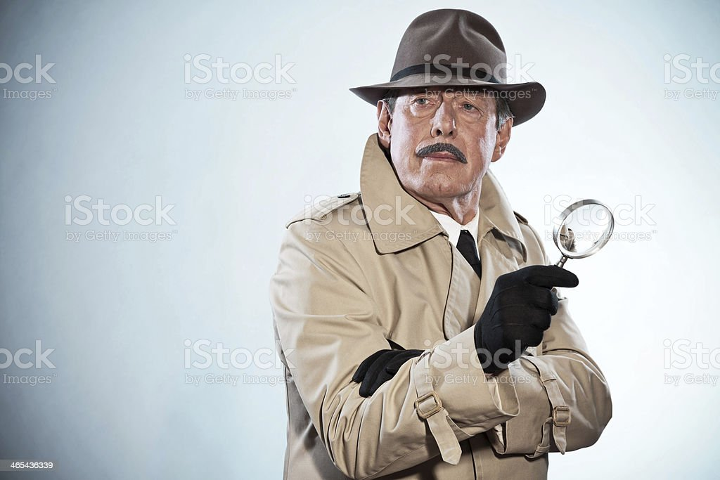 Retro detective man with mustache and hat. Holding magnifying glass. stock photo