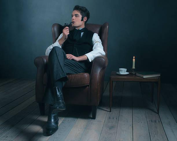 retro dickens style man smoking pipe. sitting in leather chair. - charles dickens weihnachtsgeschichte stock-fotos und bilder