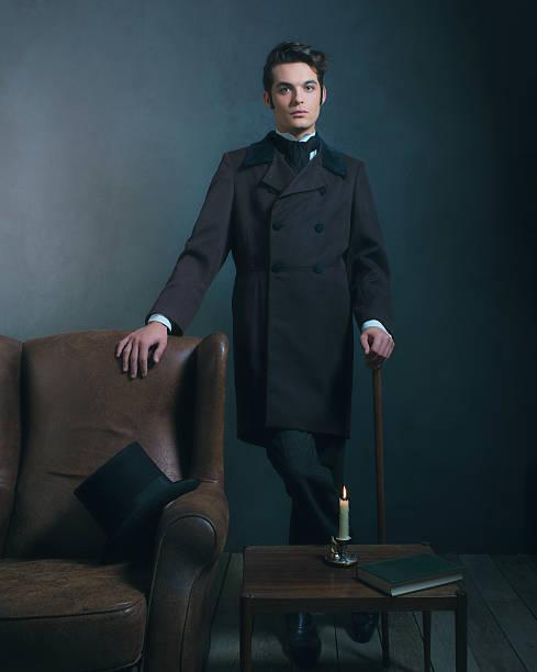 retro dickens style man standing with cane next to chair. - charles dickens weihnachtsgeschichte stock-fotos und bilder