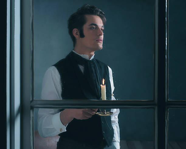 retro dickens style man with candlestick looking out rainy window. - charles dickens weihnachtsgeschichte stock-fotos und bilder