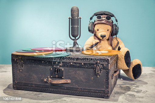 1043737676 istock photo Retro DJ Teddy Bear toy with leather aviator's hat, headphones and goggles and studio microphone, vinyl disk records on old aged classic travel trunk. Vintage style filtered photo 1067401846