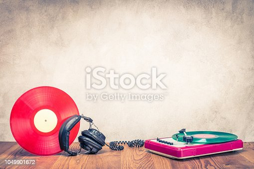 1043737676 istock photo Retro DJ turnable mixer, old headphones and red vinyl disc on wooden table. Vintage style filtered photo 1049901672
