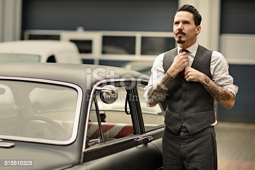 istock Retro dressed man with moustaches posing next his car 515515325