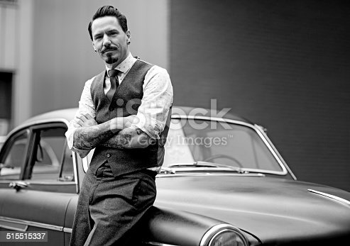 istock Retro dressed man with moustaches posing next his car 515515337