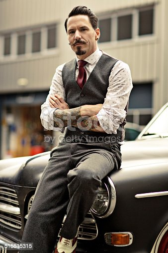 istock Retro dressed man with moustaches sitting on his car 515515315