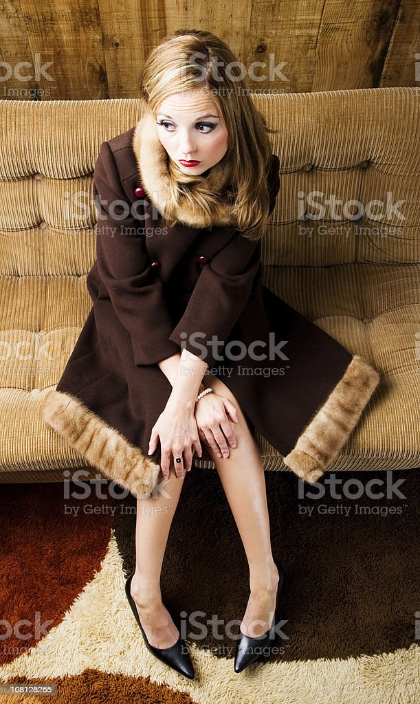 Retro Dressed Young Woman Sitting on Couch royalty-free stock photo