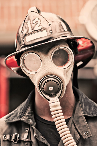 Toned image of a retro emergency response worker with gas mask.