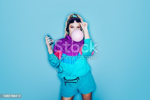 A woman wearing clothing styled after the 1980's and 1990's listens to music on her personal cassette tape player in front of a large bright blue background. She blows a large pink bubble with her chewing gum.  Shot with a ring flash.