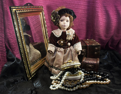 Retro fashioned porcelain doll with jewelry box.