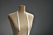 Retro female tailor's mannequin torso with measuring tape, dark gray background. Copy space. Little noise visible.