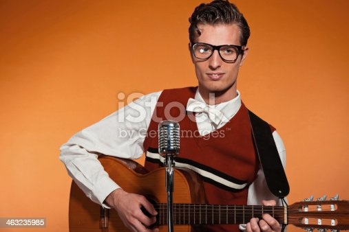 463242403 istock photo Retro fifties musician with glasses playing acoustic guitar. 463235985