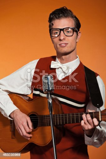 463242403 istock photo Retro fifties musician with glasses playing acoustic guitar. 463235989
