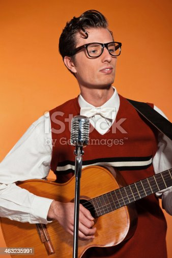463242403 istock photo Retro fifties musician with glasses playing acoustic guitar. 463235991