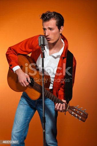 463242403 istock photo Retro fifties rock and roll singer playing accoustic guitar. 463202631