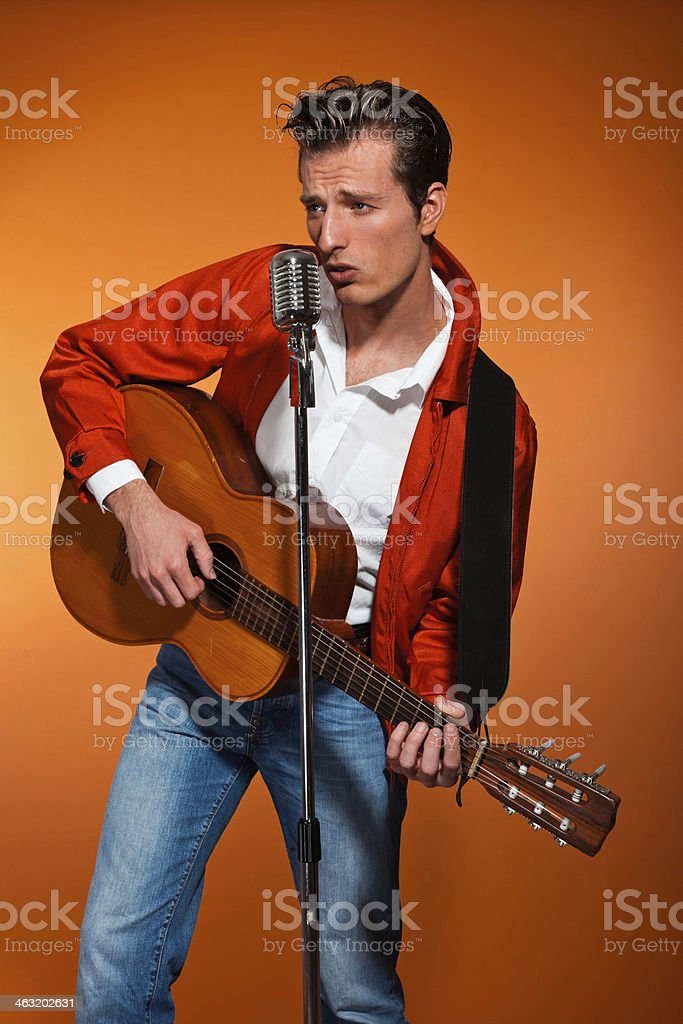 Retro fifties rock and roll singer playing accoustic guitar. stock photo