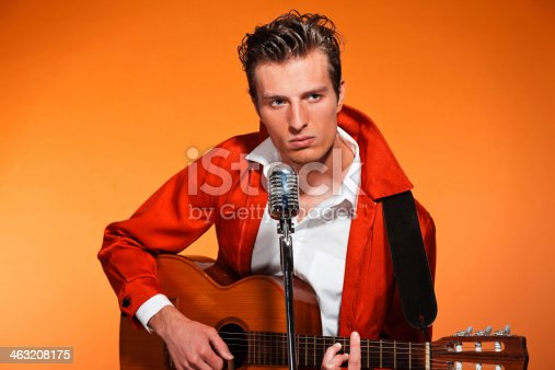 463242403 istock photo Retro fifties rock and roll singer playing accoustic guitar. 463208175
