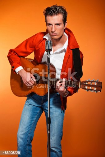 463242403 istock photo Retro fifties rock and roll singer playing accoustic guitar. 463208229