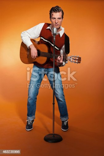 463242403 istock photo Retro fifties rock and roll singer playing accoustic guitar. 463235995