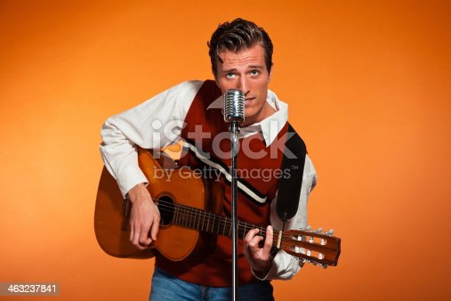 463242403 istock photo Retro fifties rock and roll singer playing accoustic guitar. 463237841