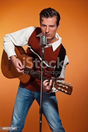 463242403 istock photo Retro fifties rock and roll singer playing accoustic guitar. 463237861