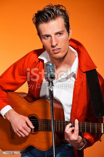 463242403 istock photo Retro fifties rock and roll singer playing accoustic guitar. 463237865