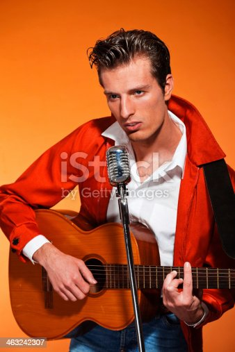 463242403 istock photo Retro fifties rock and roll singer playing accoustic guitar. 463242307