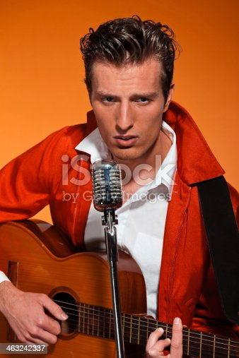 463242403 istock photo Retro fifties rock and roll singer playing accoustic guitar. 463242337