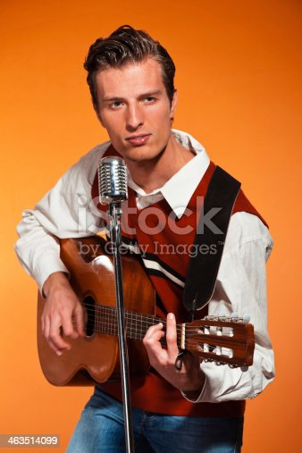 463242403 istock photo Retro fifties rock and roll singer playing accoustic guitar. 463514099