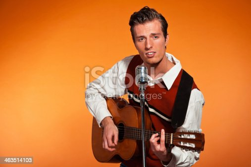 463242403 istock photo Retro fifties rock and roll singer playing accoustic guitar. 463514103