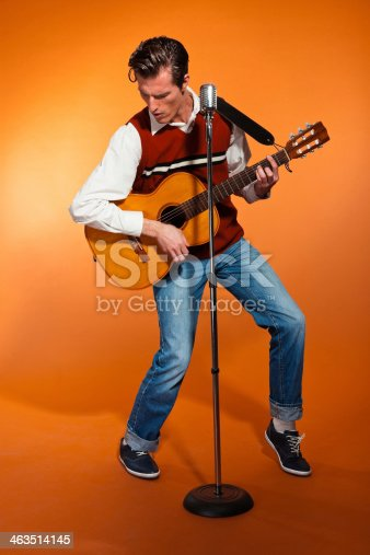 463242403 istock photo Retro fifties rock and roll singer playing accoustic guitar. 463514145