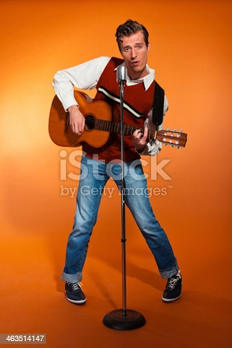 463242403 istock photo Retro fifties rock and roll singer playing accoustic guitar. 463514147